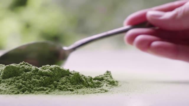 vídeos de stock, filmes e b-roll de comendo grama de cevada de chão com colher. - antioxidante