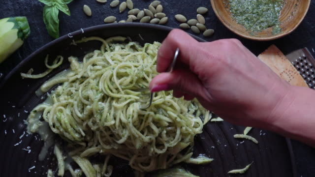 eating healthy zucchini noodles with pesto - zucchini video stock e b–roll