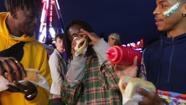 Eating Hotdogs at a Festival Three diverse young men are eating hotdogs from a food stall at a music festival. hot dog stock videos & royalty-free footage