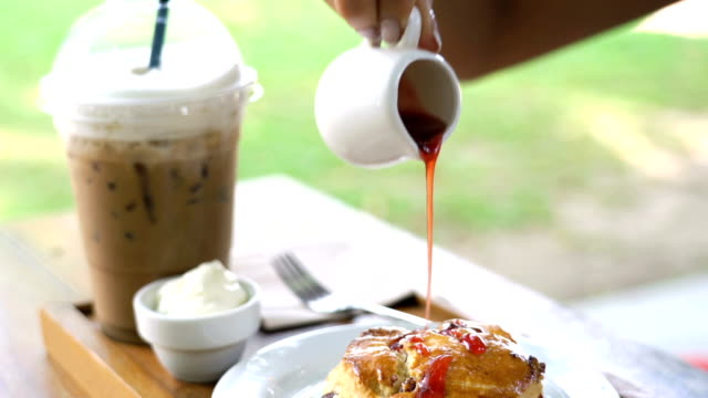 Eating iced coffee and scone with jam. video