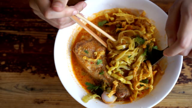 Eating Khao soi,  Thai Northern Noodle Khao soi made with a mix of deep-fried crispy egg noodles and boiled egg noodles, pickled mustard greens, shallots, lime, ground chillies fried in oil, and meat in a curry-like sauce containing coconut milk. The curry is somewhat similar to that of yellow or massaman curry but of a thinner consistency. It is popular as a street dish eaten by Thai people in northern Thailand, though not frequently served in Thai restaurants abroad. red onions stock videos & royalty-free footage