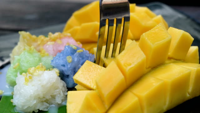 Eating mango sticky rice, Thailand food. 4K Eating mango sticky rice, Thailand food. stick plant part stock videos & royalty-free footage