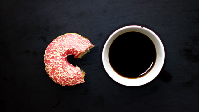 Eating pink donut and drinking a cup of coffee on dark background view from above, stop motion animation