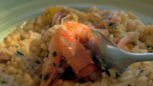 Eating risotto with squid and prawns in sea food restaurant video