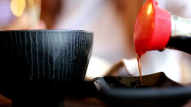 vídeos de stock e filmes b-roll de comer salmão sushi verter o molho de soja - molho arranjo