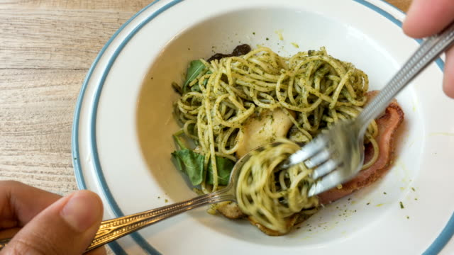 T/L eating spaghetti with pesto sauce and bacon video