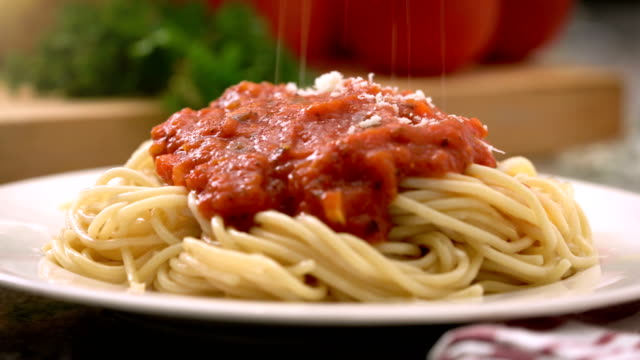 Eating spaghetti with tomato sauce Italian food Plate of spaghetti with hot tomato sauce or marinara sauce and parmesan cheese being grated on top. spaghetti stock videos & royalty-free footage