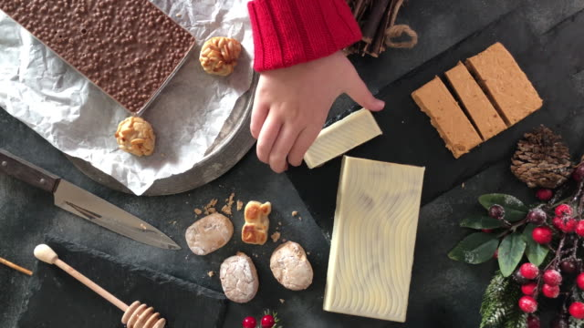Eating Spanish Christmas sweets, turron, marzipan and polvorones Eating Spanish Christmas sweets, turron, marzipan and polvorones. Flat lay pine nut stock videos & royalty-free footage