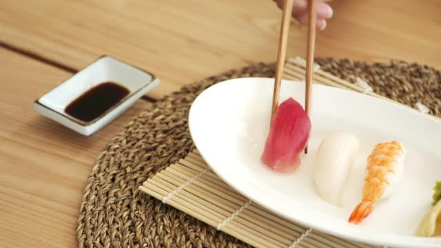 vídeos de stock e filmes b-roll de eating sushi - comida asiática