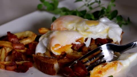 vídeos y material grabado en eventos de stock de comer sándwich de pan tostado con dos huevos poché, papas fritas y tocino - desayuno