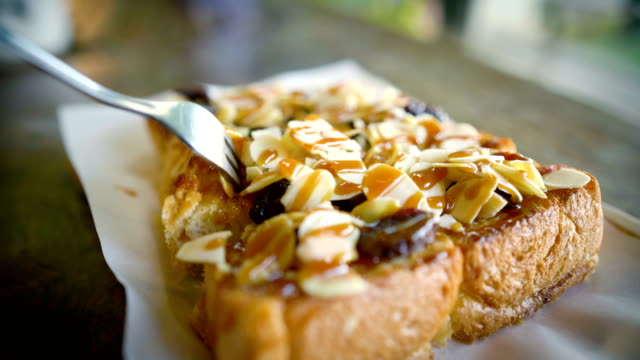 Eating Toast with caramel and almond. video