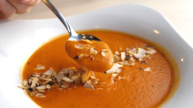 mangiare zuppa di crema di pomodoro con un cucchiaio. primo piano - paprica video stock e b–roll