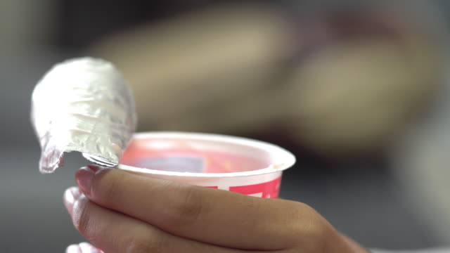eating yogurt from a plastic cup - łyżka sztućce filmów i materiałów b-roll