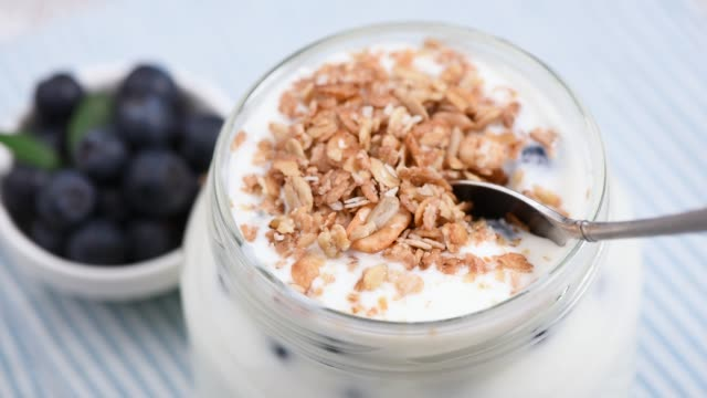vídeos de stock e filmes b-roll de eating yogurt with granola and berries in jar - oats