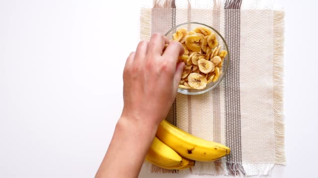 eats dried Banana Chips. Concept of healthy food, healthy lifestyle. top view flat lay