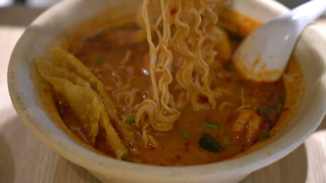 eatting spicy instant noodle (Tom Yum Kung)