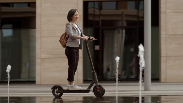 eco friendly vehicle usage in urban area - monopattino elettrico video stock e b–roll