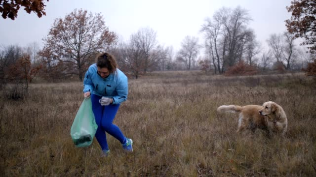 Eco friendly woman picking up litter outdoors