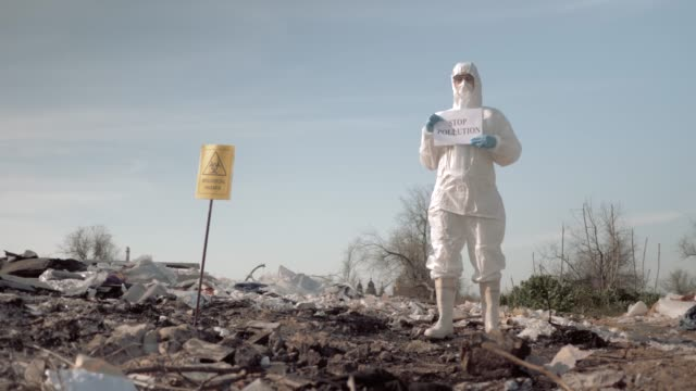 ecological disaster, woman in protective suit and mask holding poster with stop pollution slogan at landfill near sign biological hazard