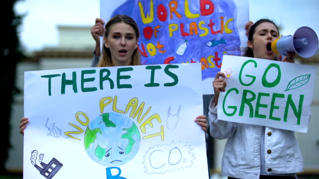 ecologists with banners shouting in megaphone about pollution, global warming - clima video stock e b–roll