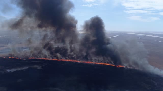 ecology disaster in nature, large fire fast moving by dry field with smoke going up to heaven near river, drone view - paradiso video stock e b–roll