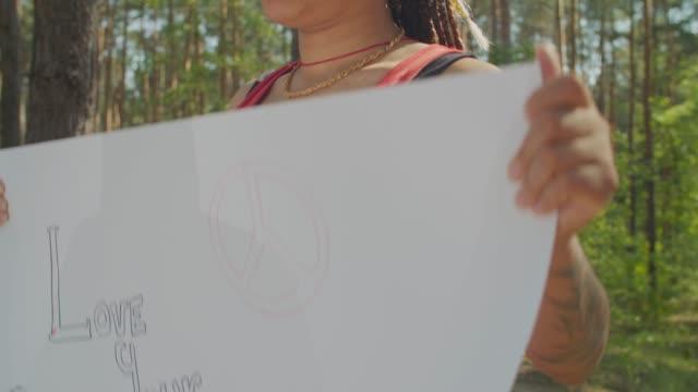 vídeos de stock, filmes e b-roll de mulher manifestante de ecologia com cartaz na floresta - consciência negra