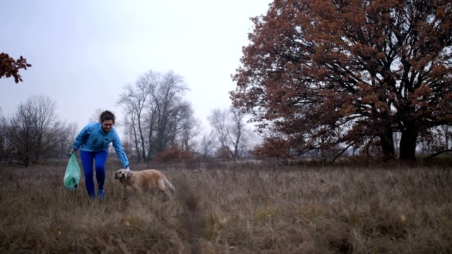 Ecology woman with dog cleaning trash in nature