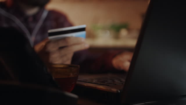 e-commerce concept. close-up shot of male hand typing number of credit card on laptop computer. payment system security business man. slow motion, 4k. - credit card filmów i materiałów b-roll
