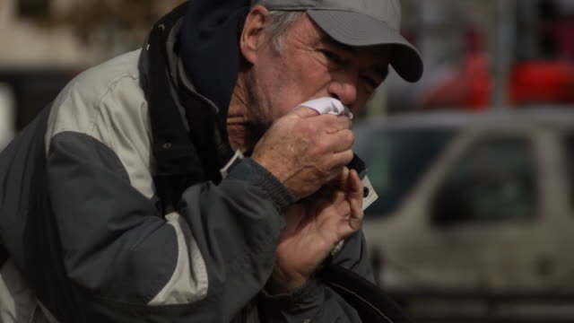Economically Distress Man Coughs in Urban Setting Medium close up of a economically distressed senior man coughing in an urban setting. coughing stock videos & royalty-free footage