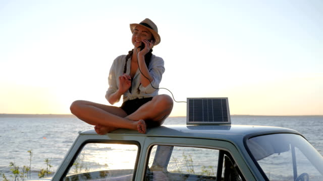 eco-tourism, young woman using powered solar cell for mobile on background blue sky, sitting on vintage car in sunlight video