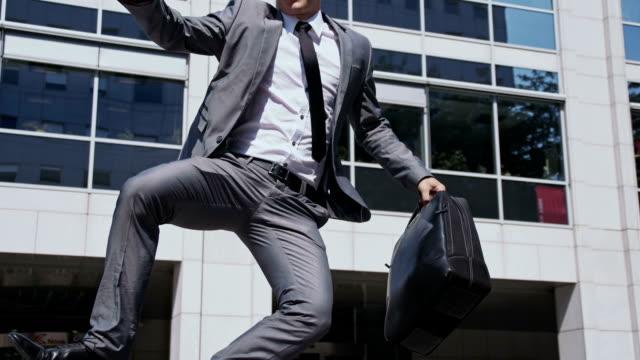 slo mo extatiska affärsman går ut ur ett kontor - kille hoppar bildbanksvideor och videomaterial från bakom kulisserna