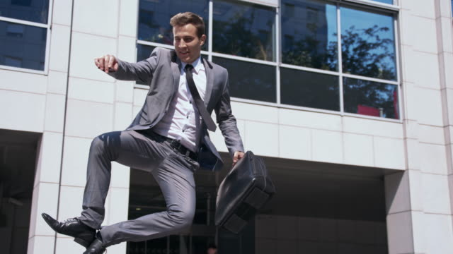 Ecstatic businessman walking out of an office video