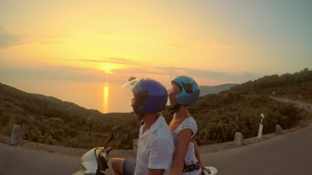 POV Ecstatic couple riding a scooter at sunset video