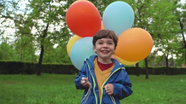 vídeos de stock, filmes e b-roll de rapaz pequeno ecstatic com balões - punhado