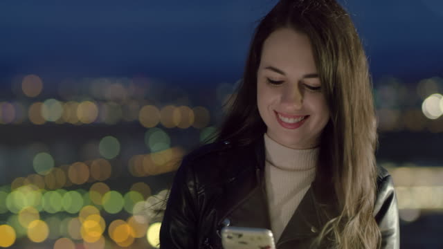LS Ecstatic young woman using a smartphone in the city at night