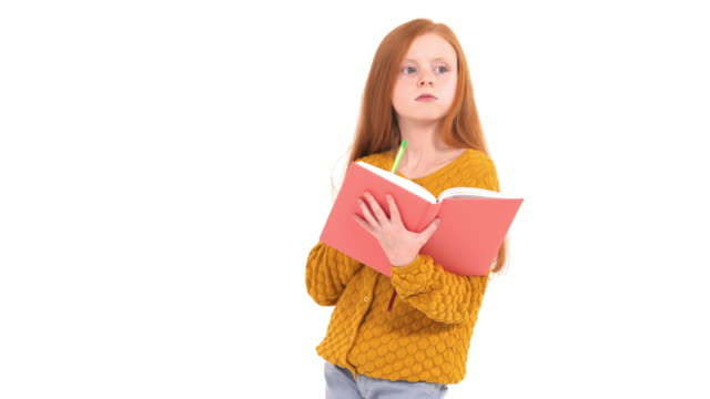 Education and homework concept. Close-up view of beautiful foxy haired school girl reading a book and thinking. Thoughtful child doing homework. Isolated, on white background