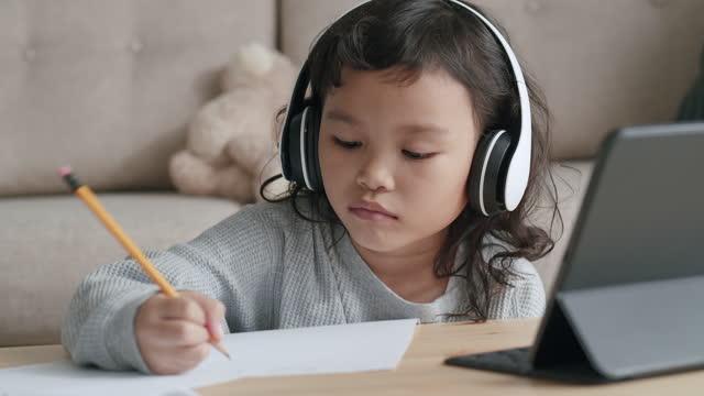 istruzione. bambina asiatica che fa i compiti usando un tablet con un auricolare al mattino. concetto di apprendimento online a casa - didattica a distanza video stock e b–roll
