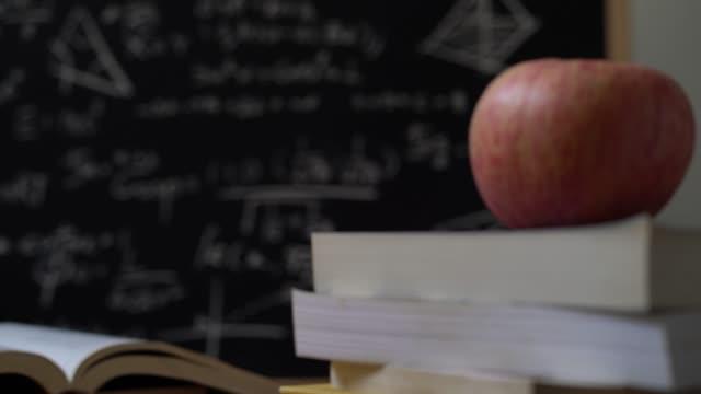 교육 배경 개념입니다. 많은 수학 공식 칠판 앞에 책의 스태킹에 애플. 슬로우 모션으로 돌리 샷. - formula 1 스톡 비디오 및 b-롤 화면