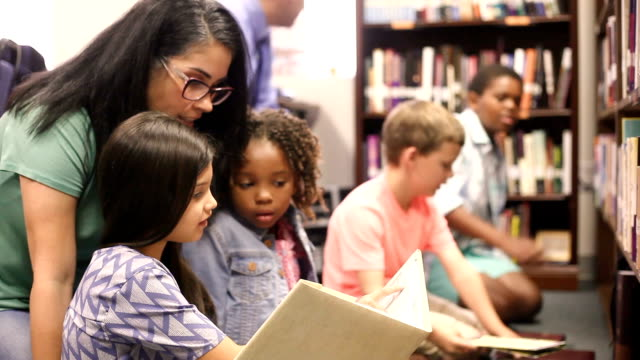 Education. brarian reads book to elementary students in library or classroom.