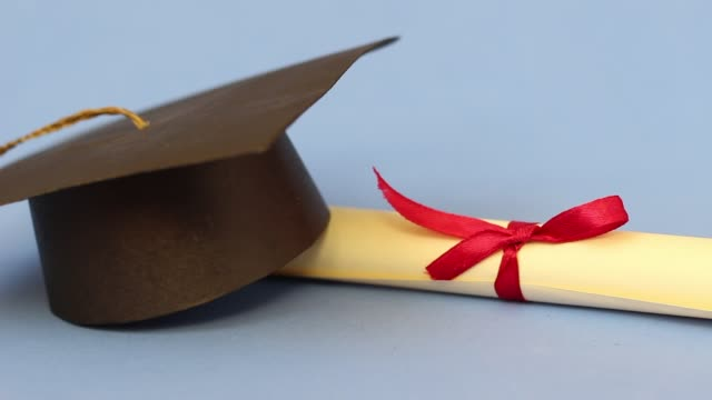 Education concept Isolated graduation cap and diploma dolly shot diploma stock videos & royalty-free footage