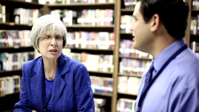 Education - Elementary school counselors  in library. Multi ethnic elementary school counselora meet in classroom or library to discuss current issues. school counselor stock videos & royalty-free footage