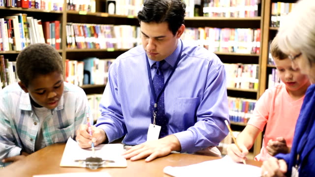 Education - Elementary school counselors with students in library. Elementary school counselors meets with a multi-ethnic group of students in classroom or library to discuss current issues. school counselor stock videos & royalty-free footage