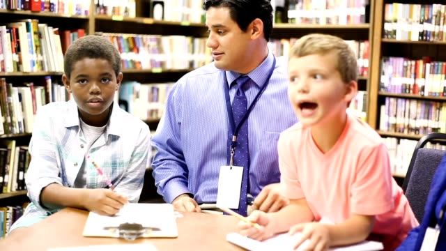 Education - Elementary school counselors with students in library. video