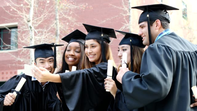 Education in United States Graduates in cap and gowns pose for pictures on graduation day.  Multi ethnic group.  Girl in group is taking a selfie. university student stock videos & royalty-free footage