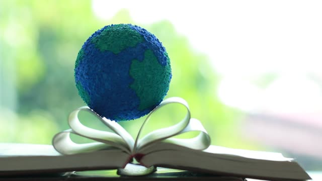 Education learning or knowledge for abroad international of university or school study concept. Globe earth model on open book with light flare on desk in home.