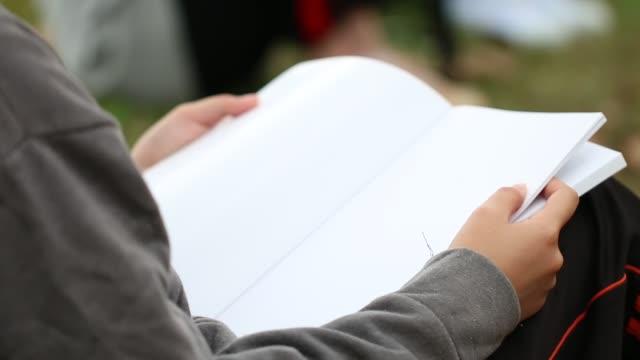 utbildning lärande studerar begrepp: asiatisk ung kvinna tänker njuta utomhus för att förbereda slutprov examen vid skolan för bok lär dig tid i sommardag. - stavning bildbanksvideor och videomaterial från bakom kulisserna