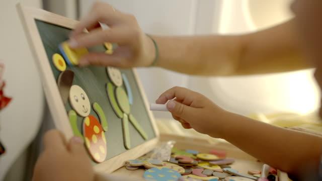 vídeos y material grabado en eventos de stock de la formación de un niño con juegos y dibujo - tablón