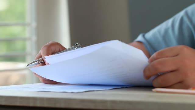 esame di prova di formazione nel concetto di scuola: studente universitario in possesso di appunti a penna foglio di documento cartaceo presso la cattedra per l'esame in aula d'esame. valutazione dell'apprendimento nelle idee di classe - esame università video stock e b–roll
