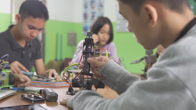 Education Topics :Smart School boy building a Small Robot arm and Uses Laptop to Program Software for Robotics Engineering Class as a school science project.science and people concept.