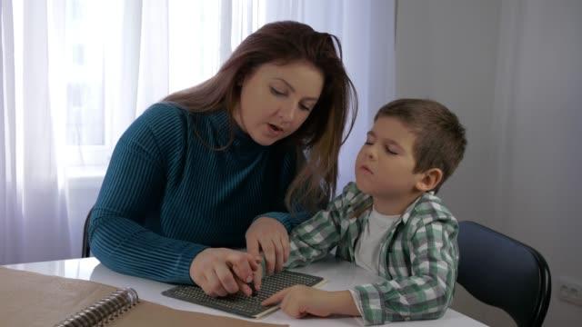 edukacja dzieci niedowidzące, mama uczy niewidomego syna chłopca do pisania znaków brajlowskich czcionki siedzącej przy stole w jasnym pokoju - store filmów i materiałów b-roll